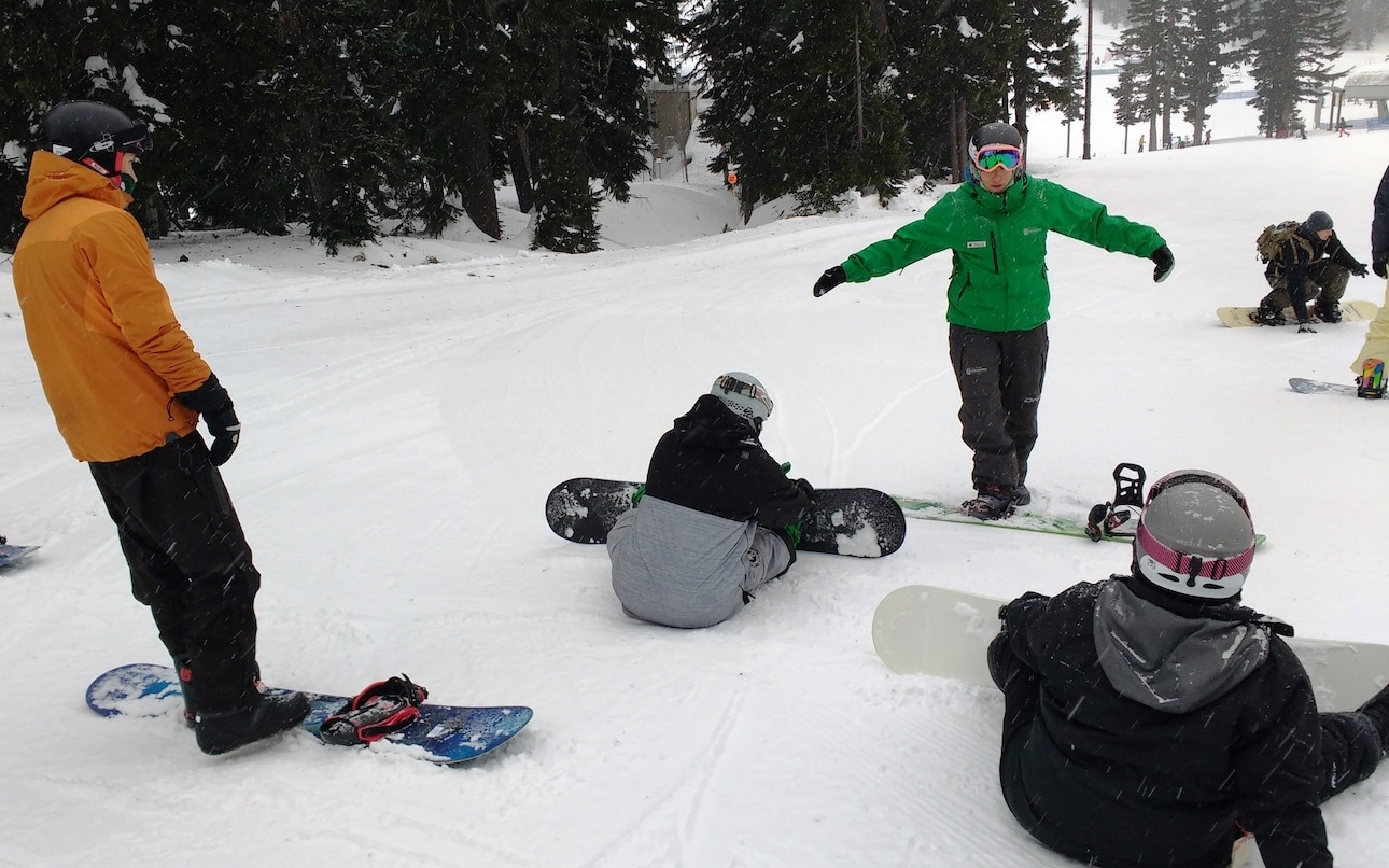 Four youth practice snowboarding on a slight incline at Mt. Hood Meadows.