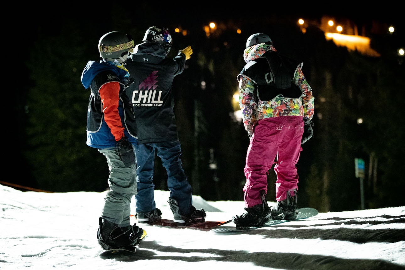 Three kids practice skills on the snow at night.