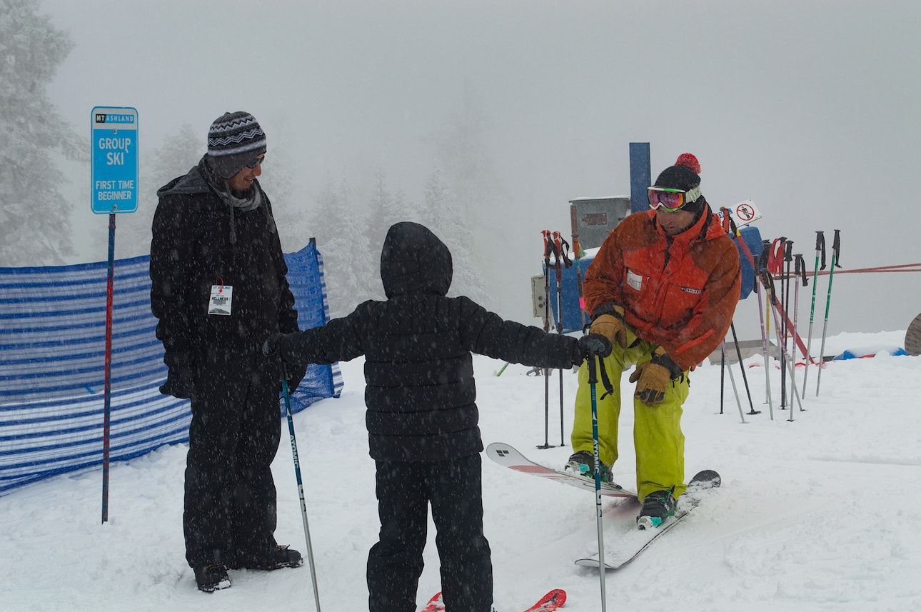 Two mentors attend to a child learning to ski at Mt. Ashland.