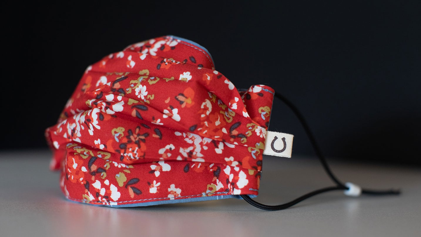 A face covering made of red fabric with flower print.