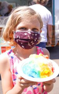 A child wears a face covering while holding a colorful shaved ice dessert.