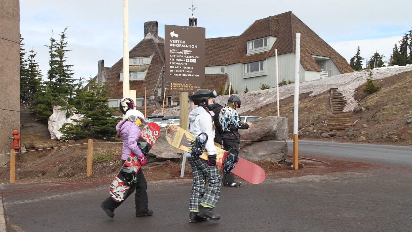 Young snowboarders wear face coverings as they walk to the lift.