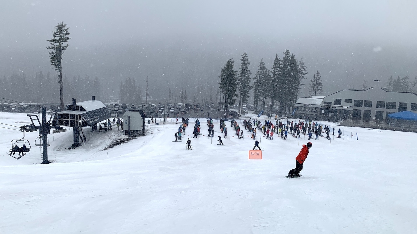 People waiting to ski are spaced out in lines.
