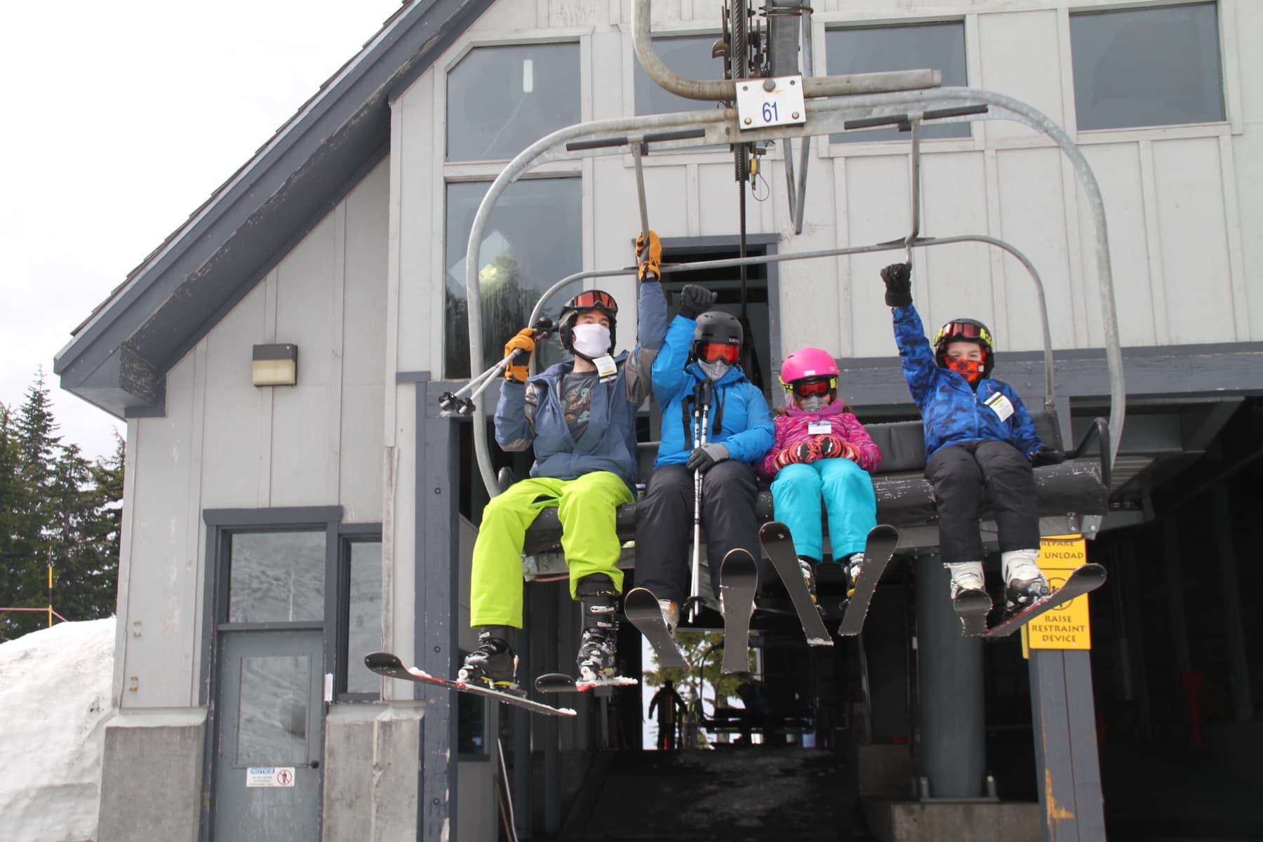 A family of four sits on a ski lift, geared up for the slopes and wearing face coverings.
