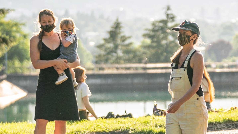 Una persona pasa junto a una familia. Todo el mundo usa máscaras.
