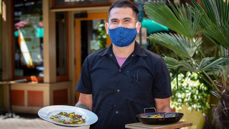 Un camarero lleva una máscara.
