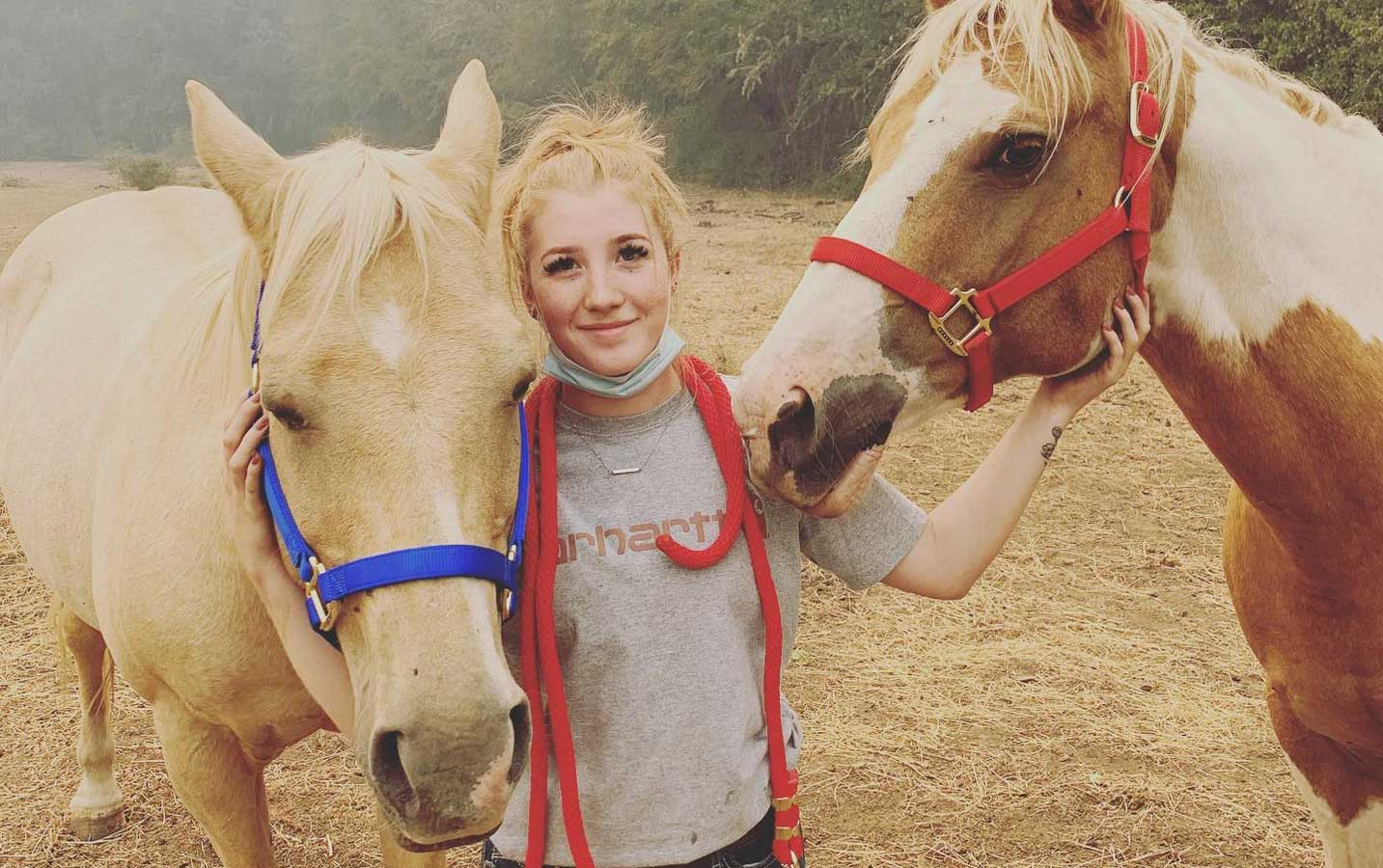 A girl smiles with two horses in the smokey haze.