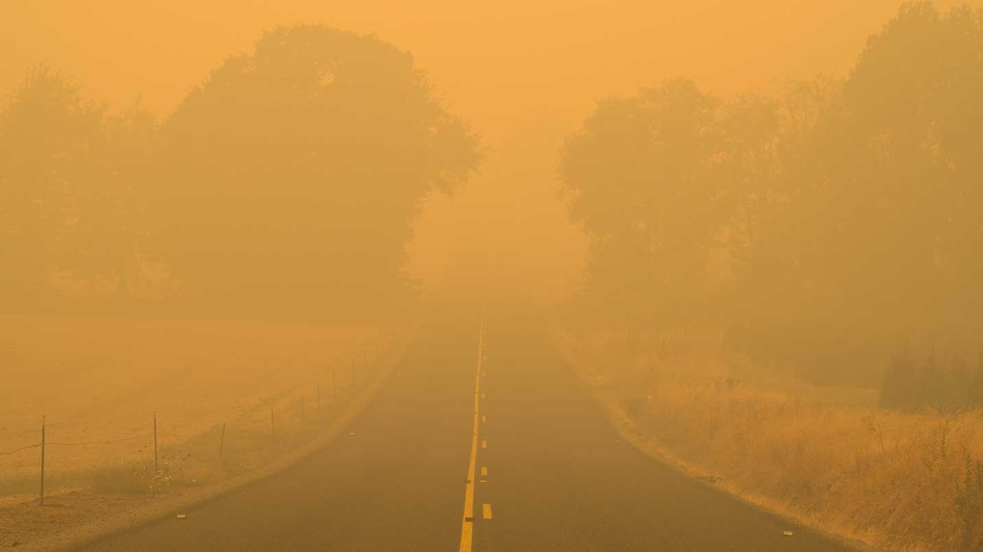 A smokey road is barely visible in an orange haze.