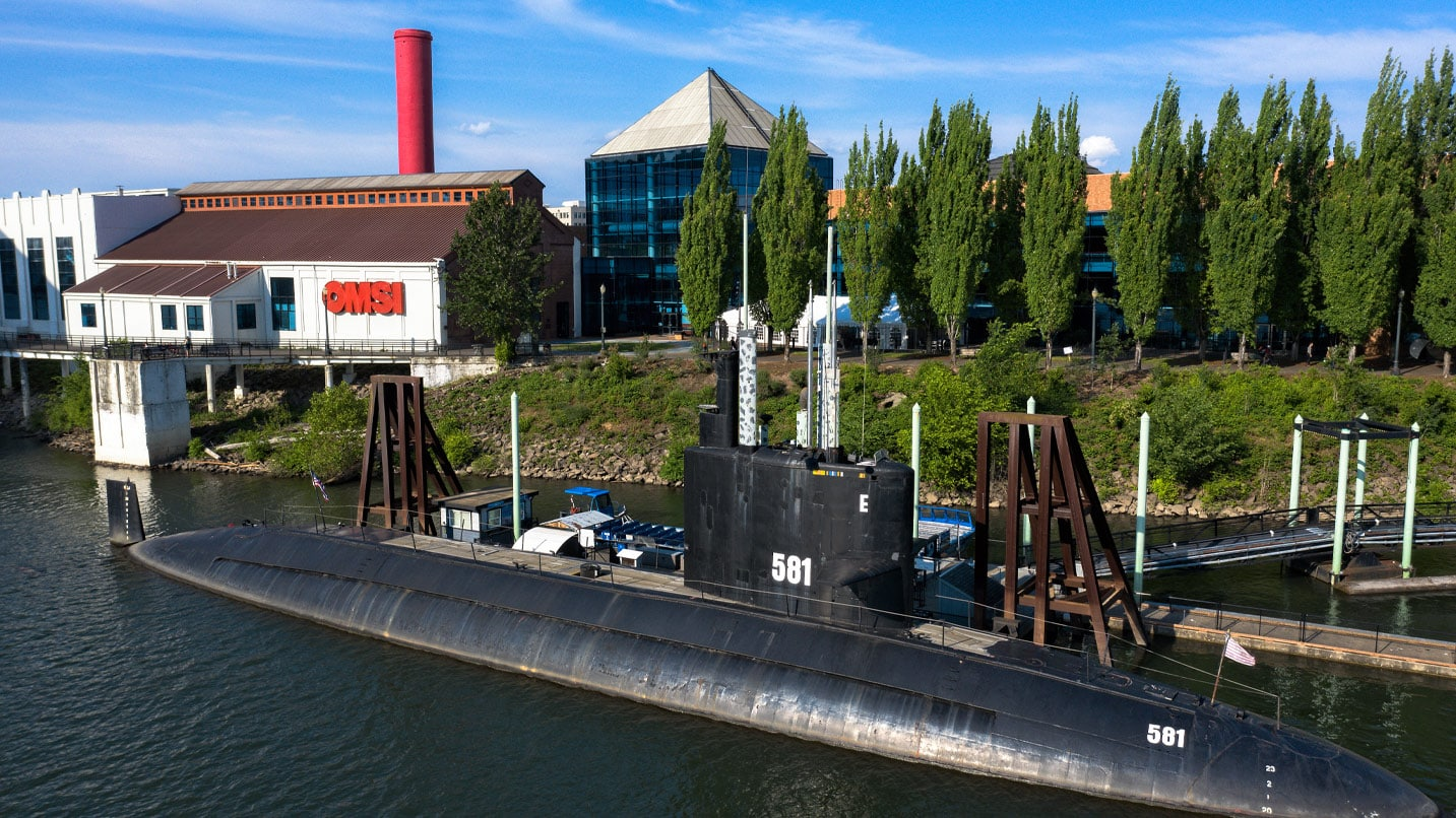Outside the Oregon Museum of Science and Industry, the USS Blueback Submarine sits in the water.