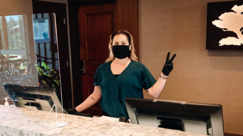 A hotel's front-desk employee wears a face covering and gloves while flashing a peace sign.
