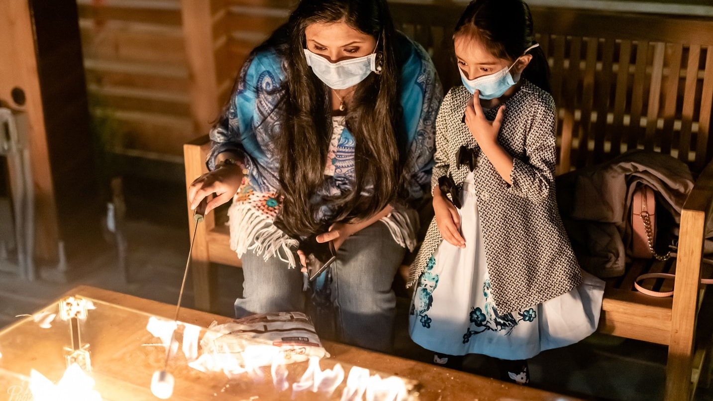 A mother and daughter look at a fire pit while wearing face coverings.