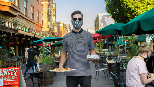 A waiter wears a face covering and holds two plates of food at an outdoor dining plaza.