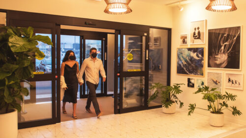A couple wears face coverings as they walk into a hotel.
