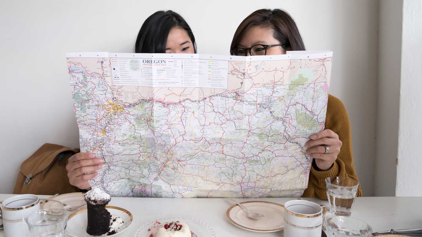 Two women look at a map of Oregon.