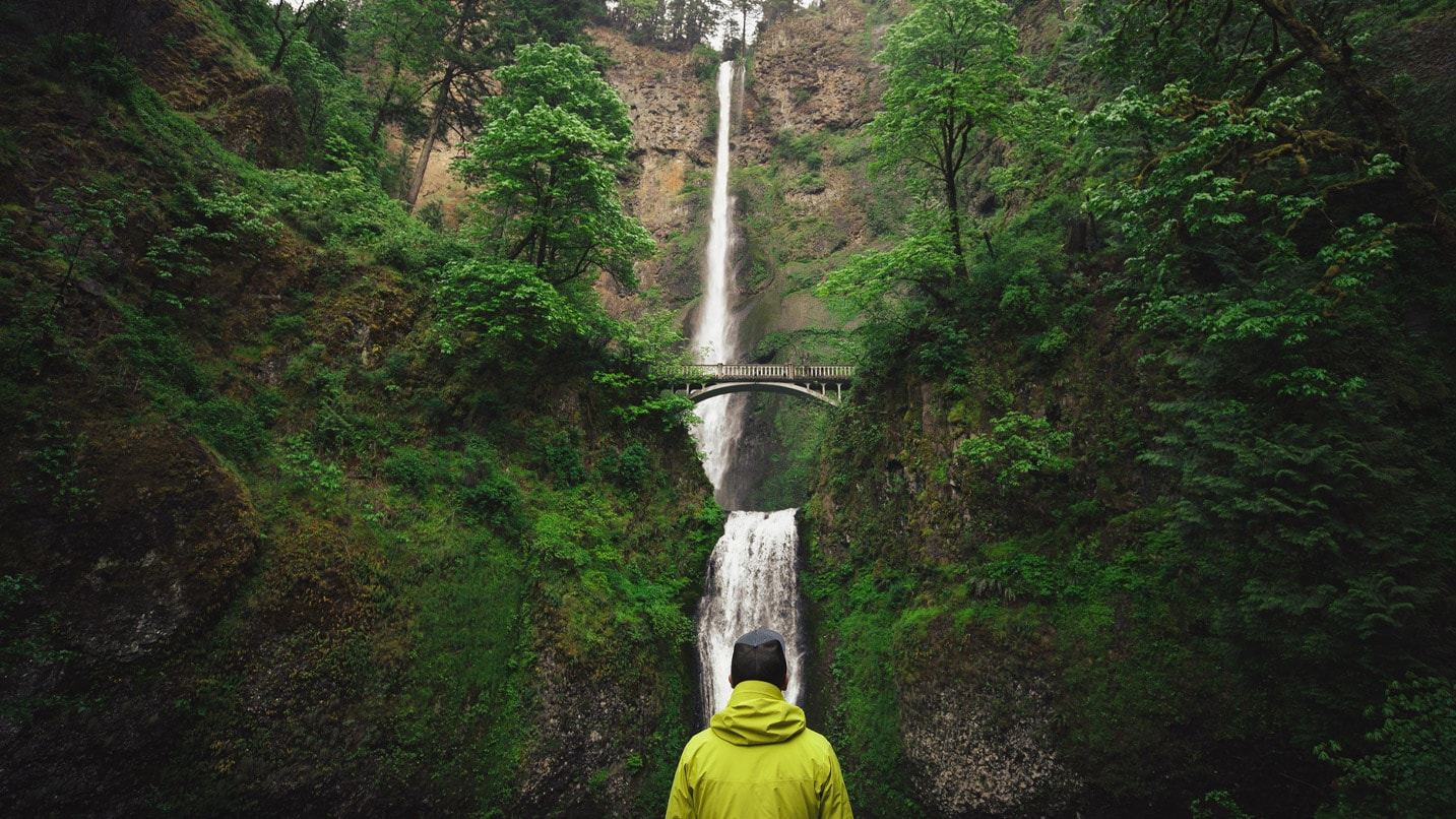A person wearing a yellow jacket looks at the two-tiered Multnomah Falls.