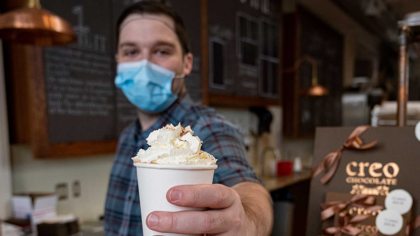 A masked person hands a cup of hot cocoa.