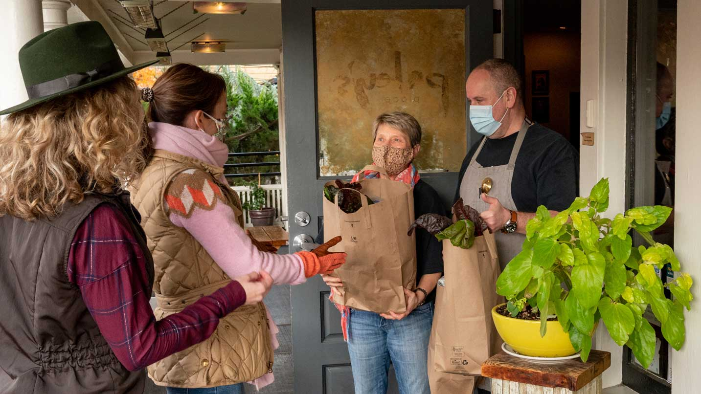 Masked people exchange a bag of a food at the entrance to a restaurant.