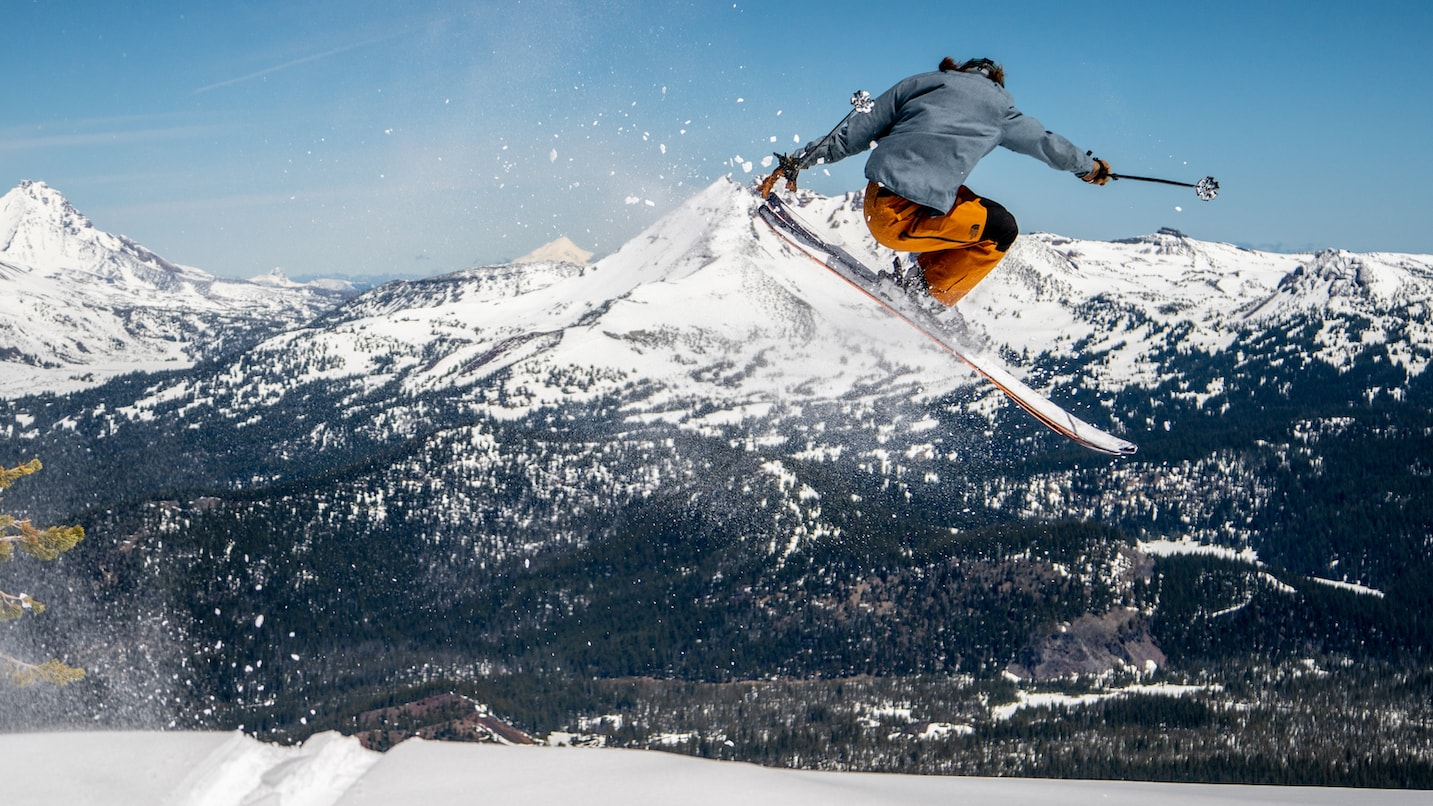 A skier gets air in front of a landscape of snowy peaks.