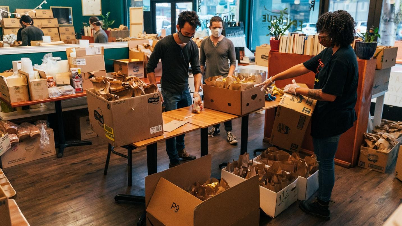 Masked volunteers pack boxes of food.