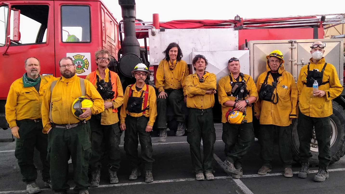 A crew of volunteer firefighter lean against a firetruck.