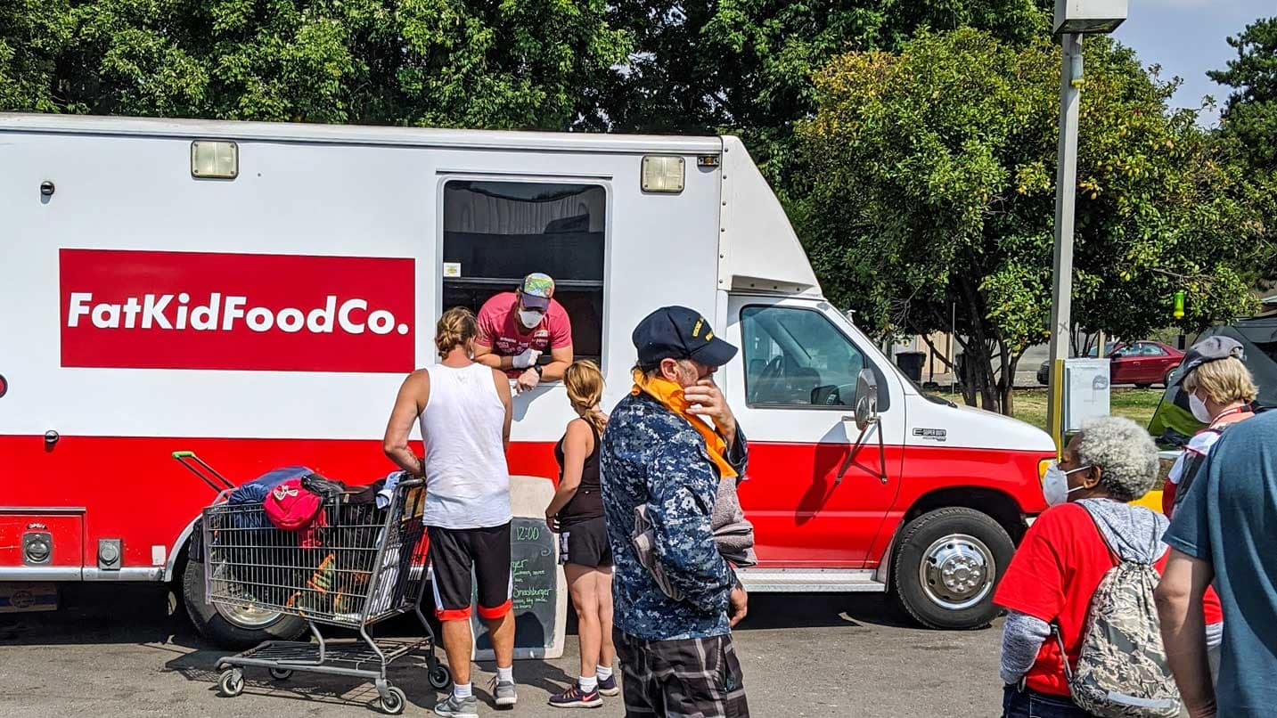 A red and white food truck serves food to masked people.