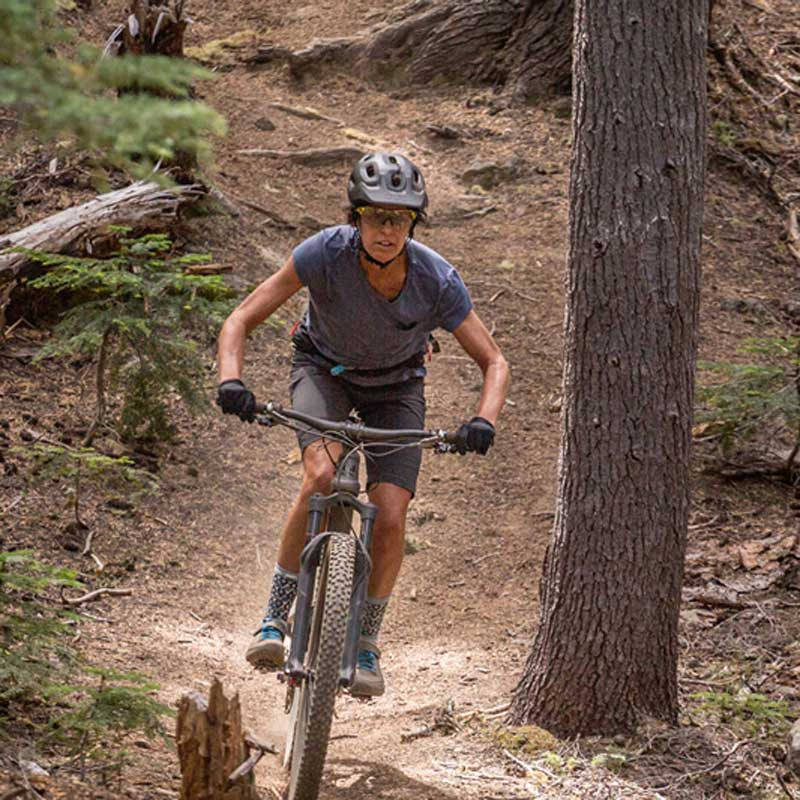 A mountain biker wears a helmet while taking on a dirt track.