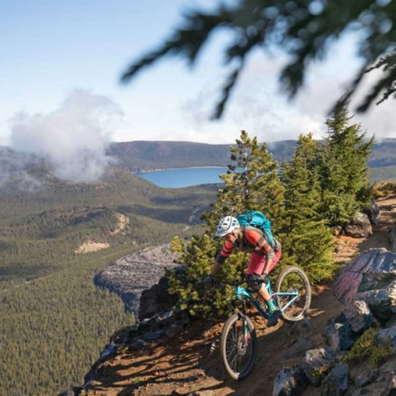 A mountain biker pedals down rocky terrain with a volcanic caldera in the background.