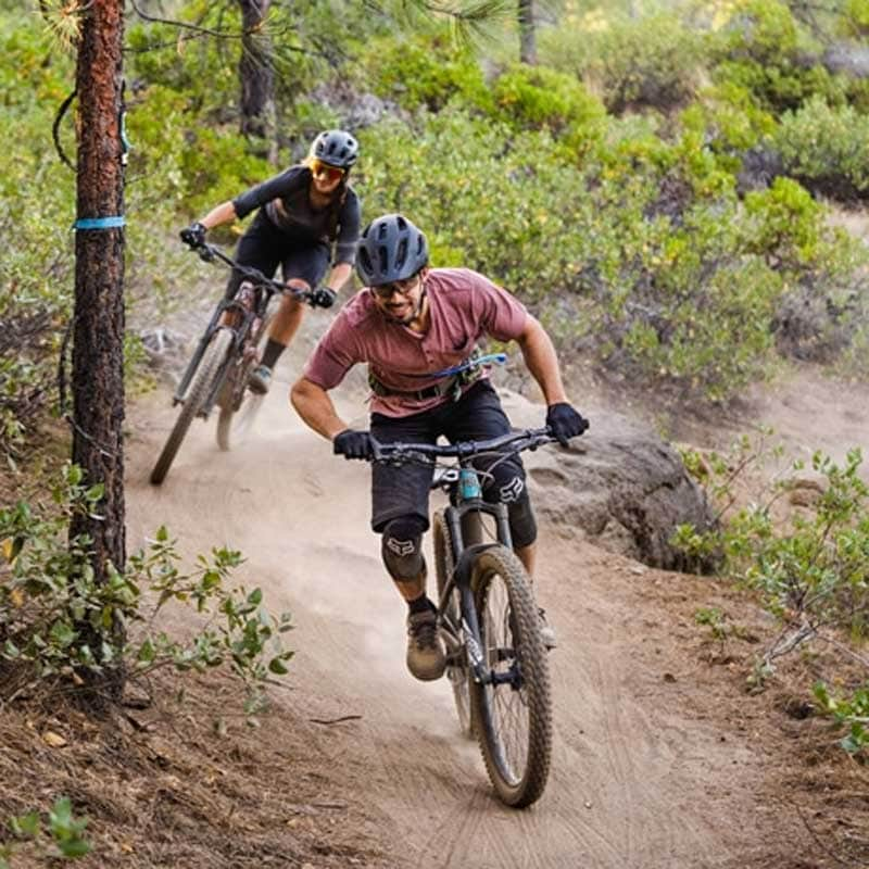 Two mountain bikers speed down a dirt track.