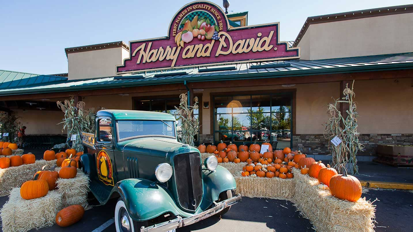 A classic truck is parked outside the Harry & David visitor center surrounded by pumpkins and hay bales.