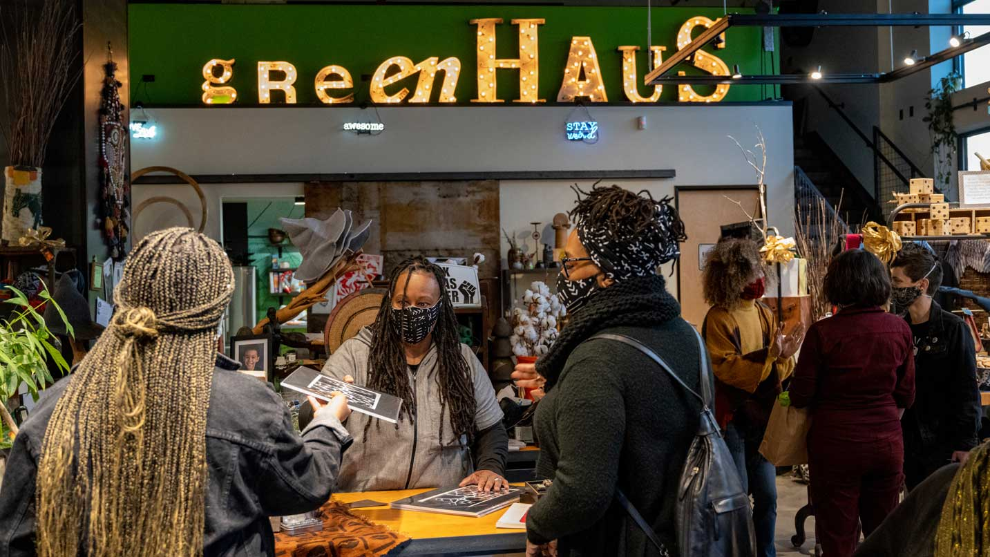Masked customers purchase art at greenHaus.