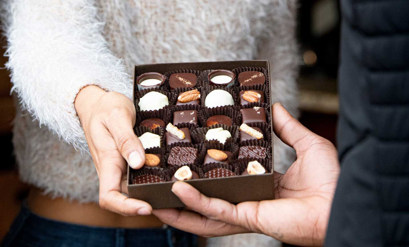 A hand passes an open box of chocolates to a friend.