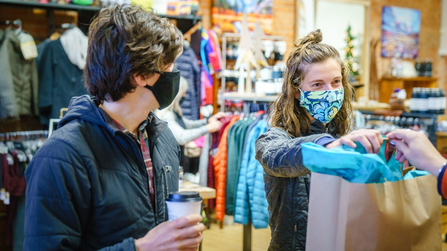 Masked customers purchase clothes at the Old Mill District.
