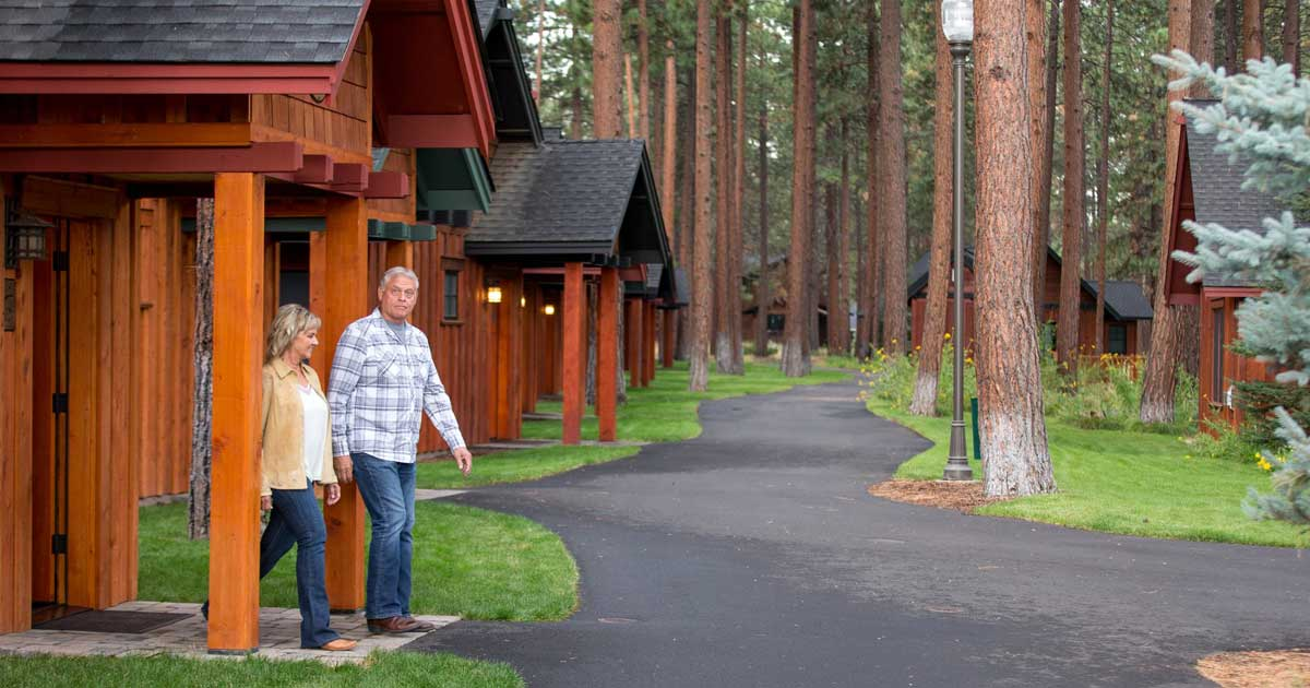 Two people walk out of their cabin.