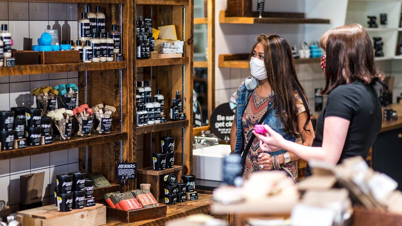 Two people wearing masks shopping