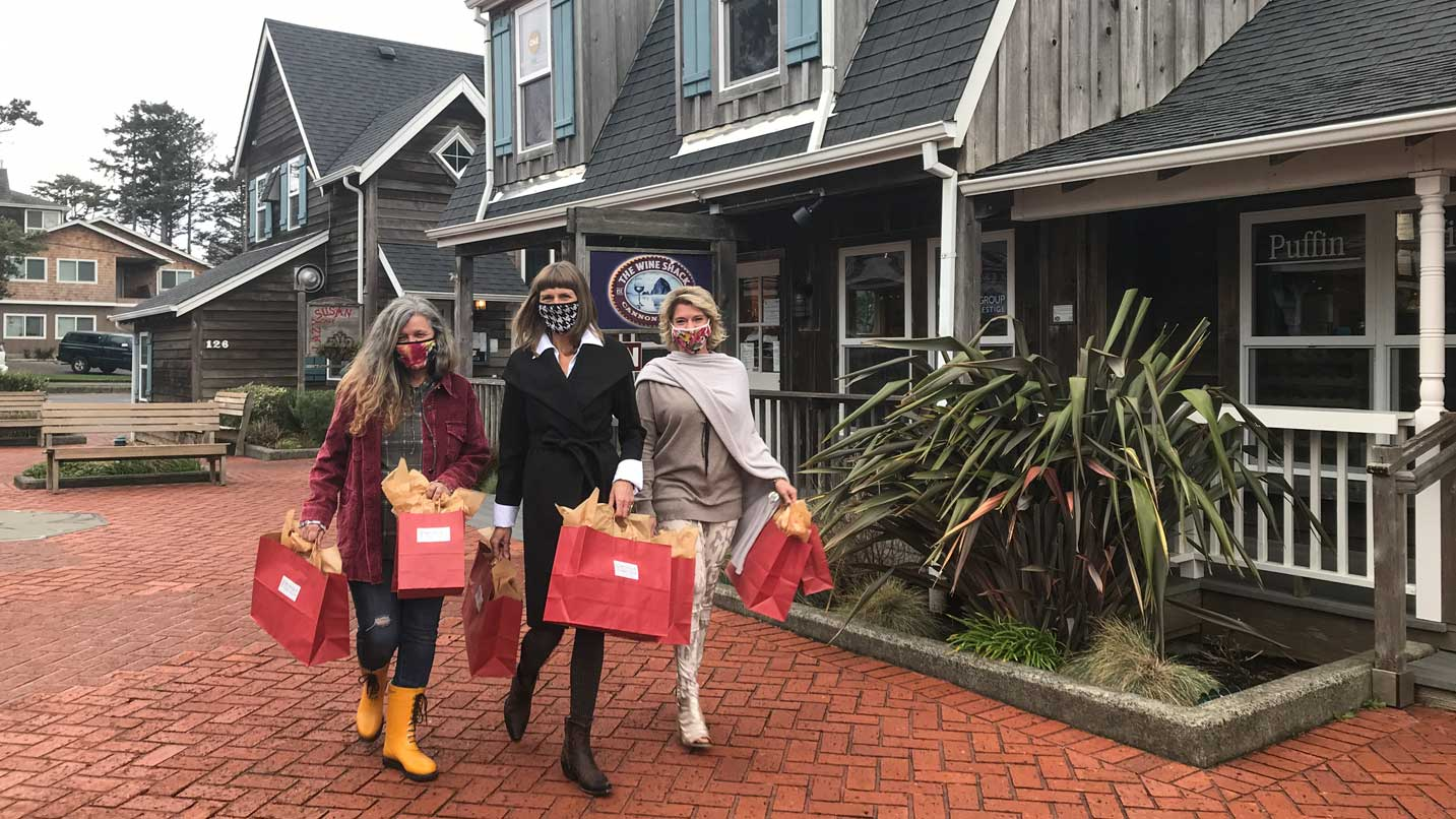 Three masked women hold shopping bags outside of a quaint shop.