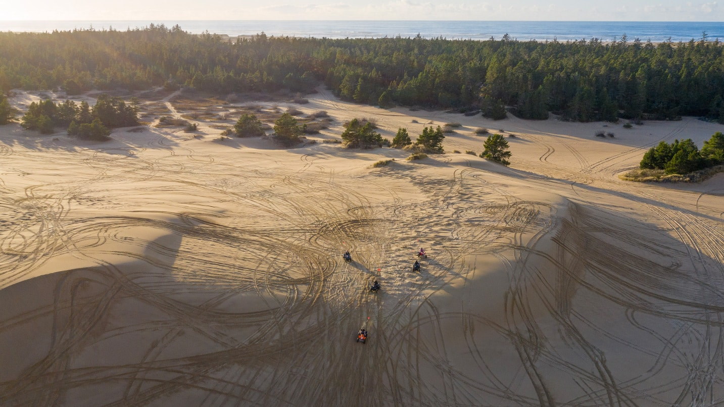 Aerial shot of dune buggies criss-crossing tracks in massive dunes with the ocean in the background.