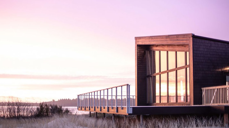 A purple sunset glows off a cabin's windows at the Oregon Coast.