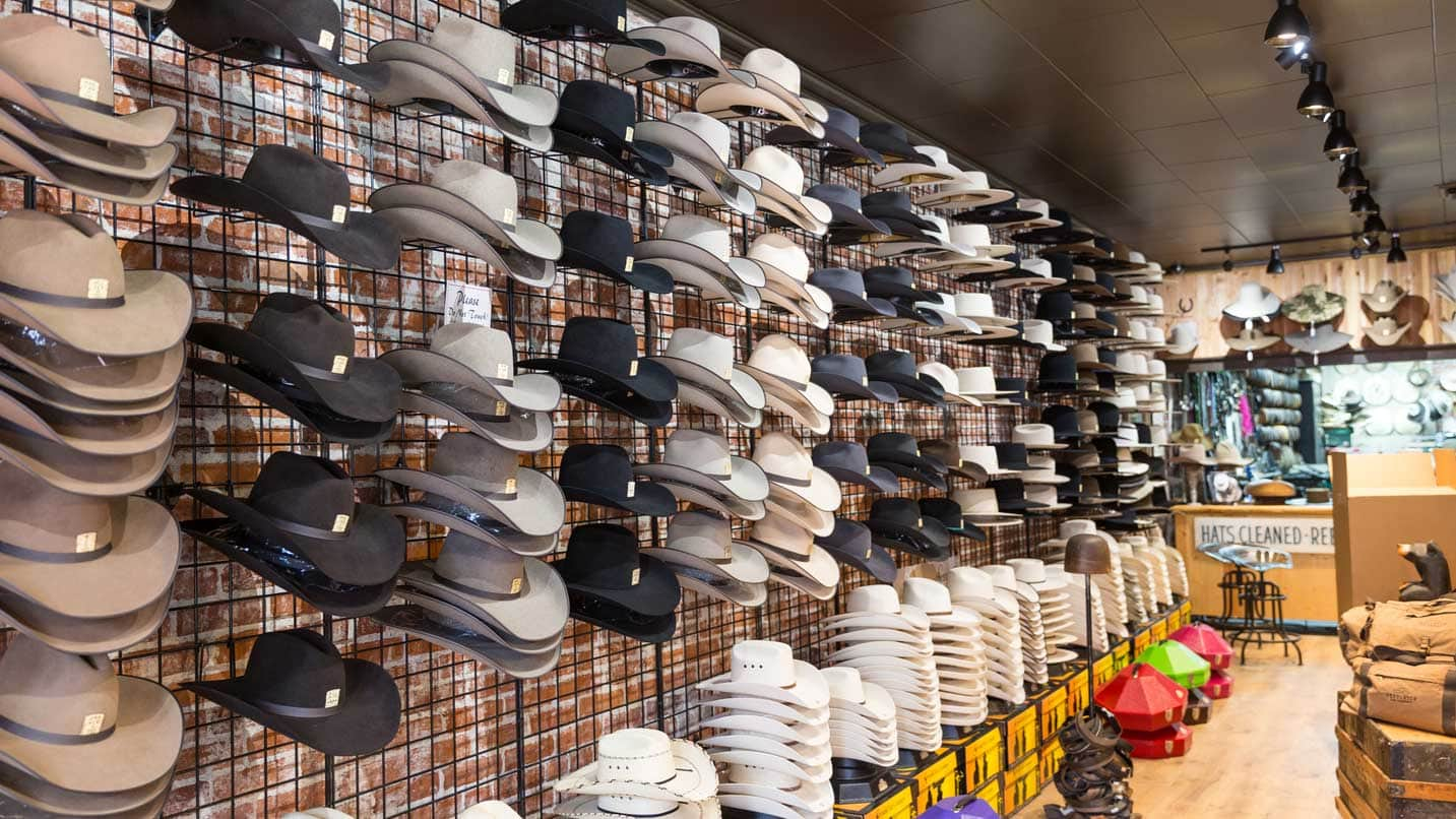 Dozens of hats hang from a wall.