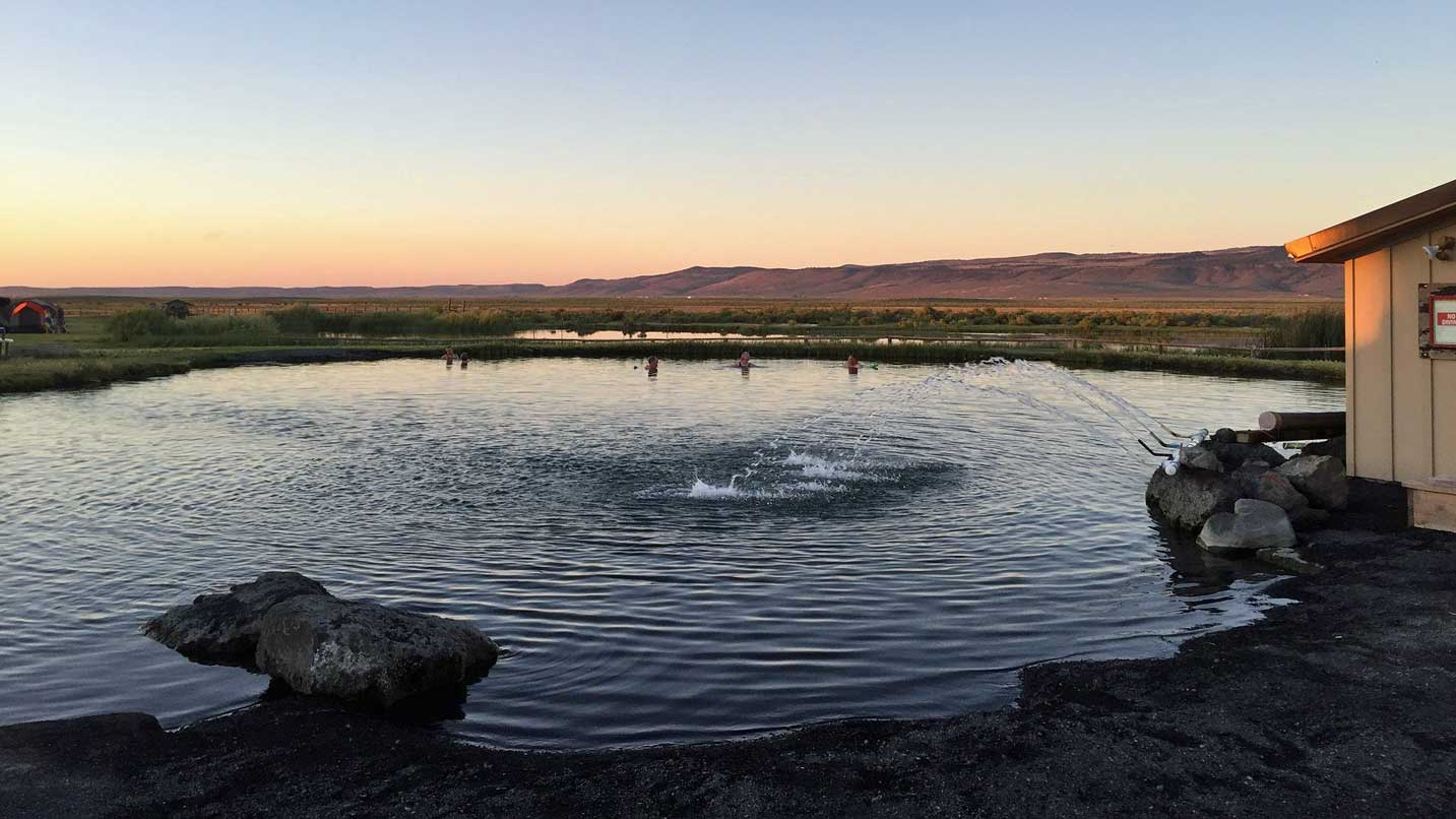 As the sun sets over the mountain range, the hot spring glows with warmth.