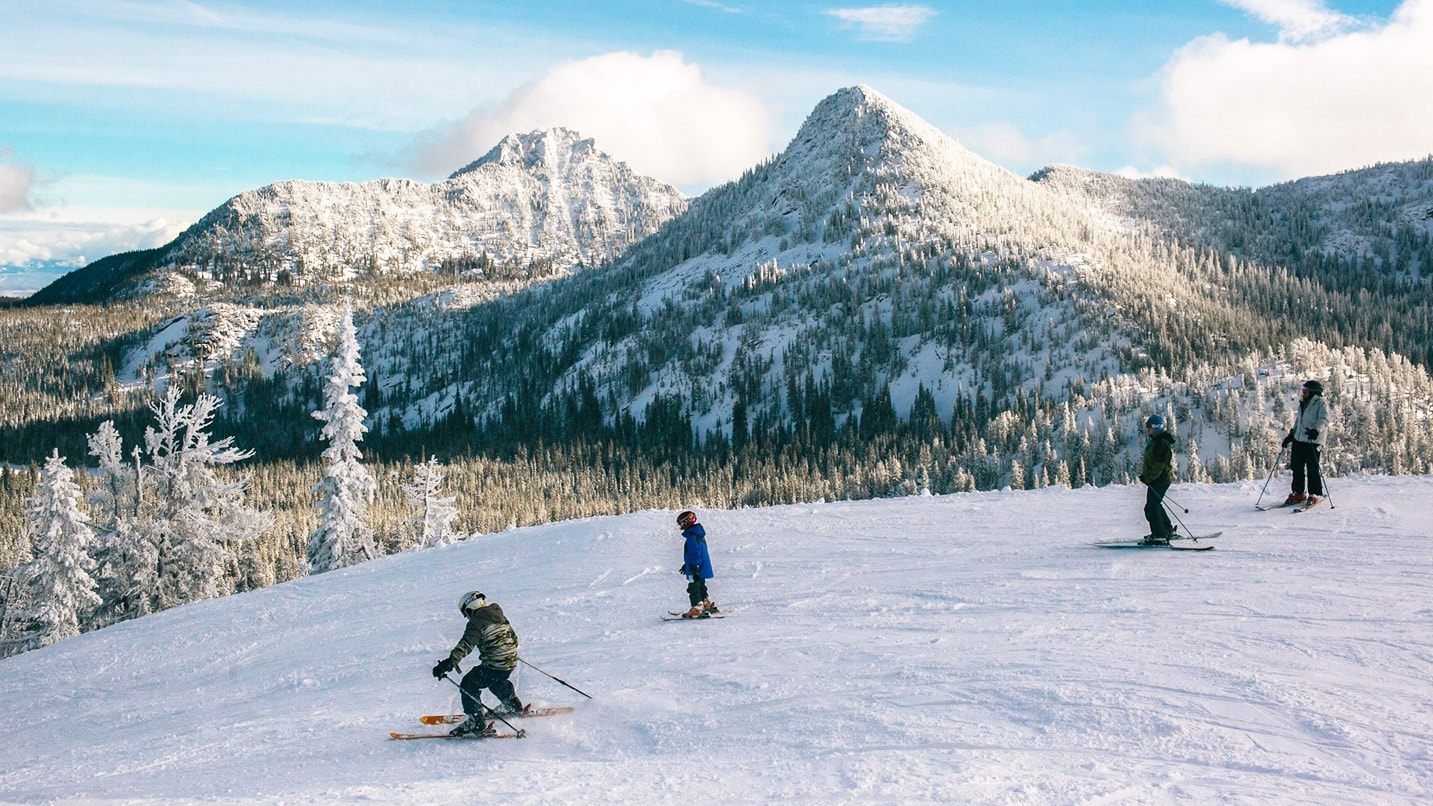 family of four skiing with mountain in background