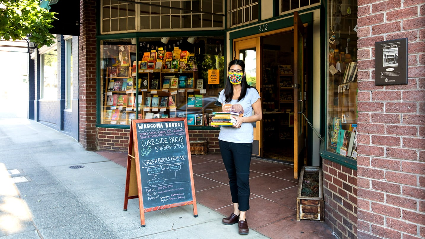 A masked person holds books outside a storefront.