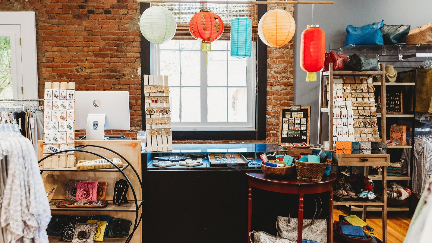 Boutique retail shop displaying clothing, jewelry and accessories with multicolored lanterns hanging from ceiling.
