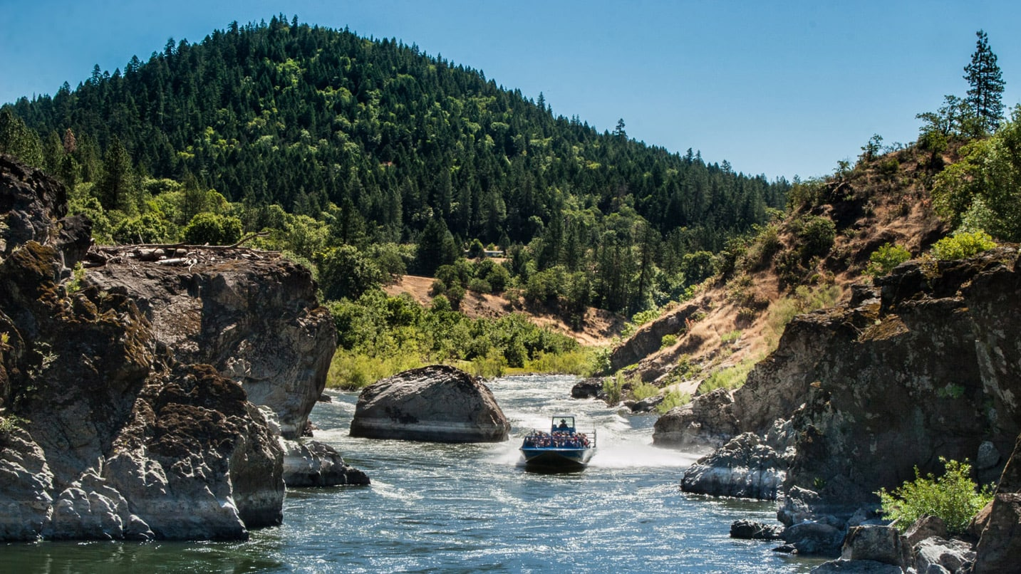 Blue jetboat crusing up the Rogue River flanked by rocky cliffs and mountain behind it.