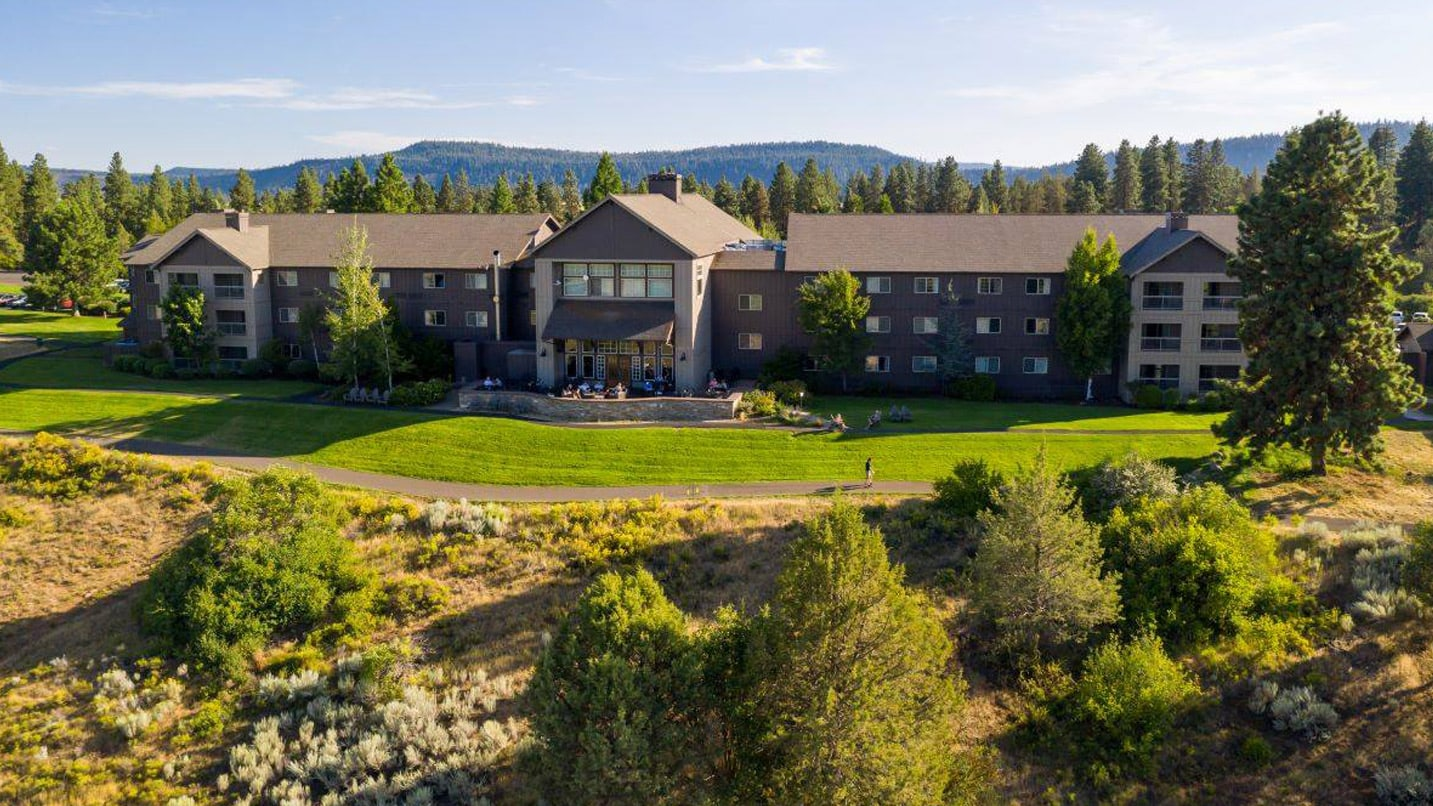 Expansive lodge on situated on beautifully manicured lawn and foothills behind it.