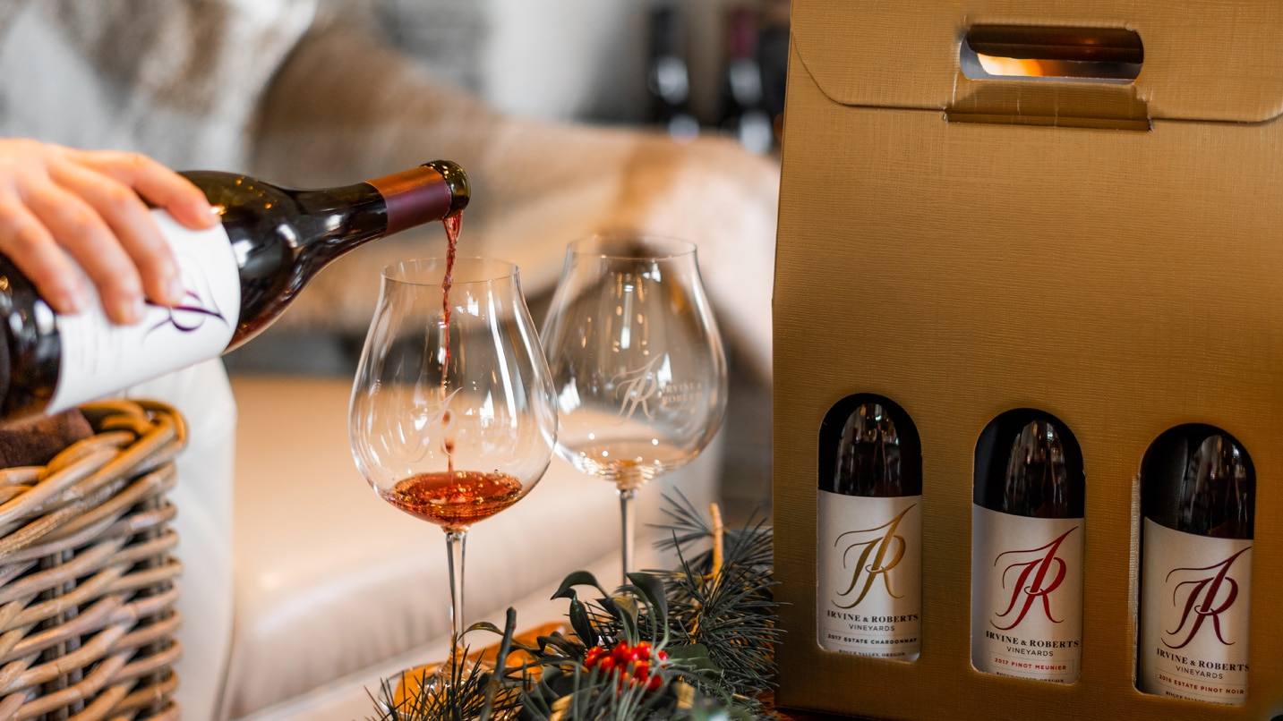 Glass of pinot noir being poured with three bottles of wine gift wrapped festively in background.