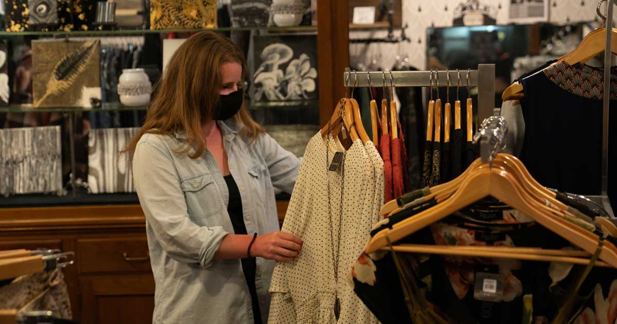 A masked customer looks at sweaters.