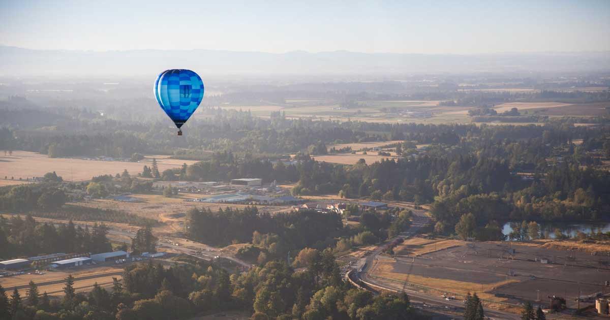 A hot air balloon soars over farmland.