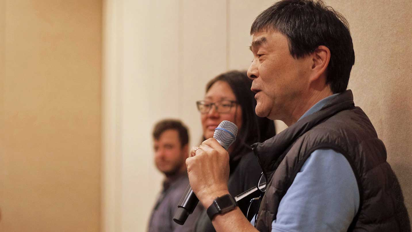 Stan Hinatsu speaks into a microphone as people watch.
