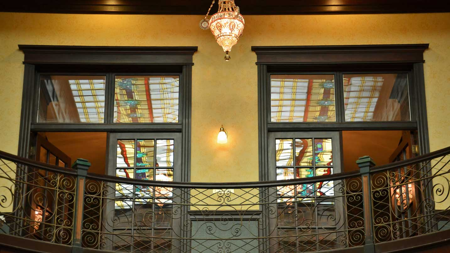 A stained glass ceiling peeks out from behind vintage wooden doors.