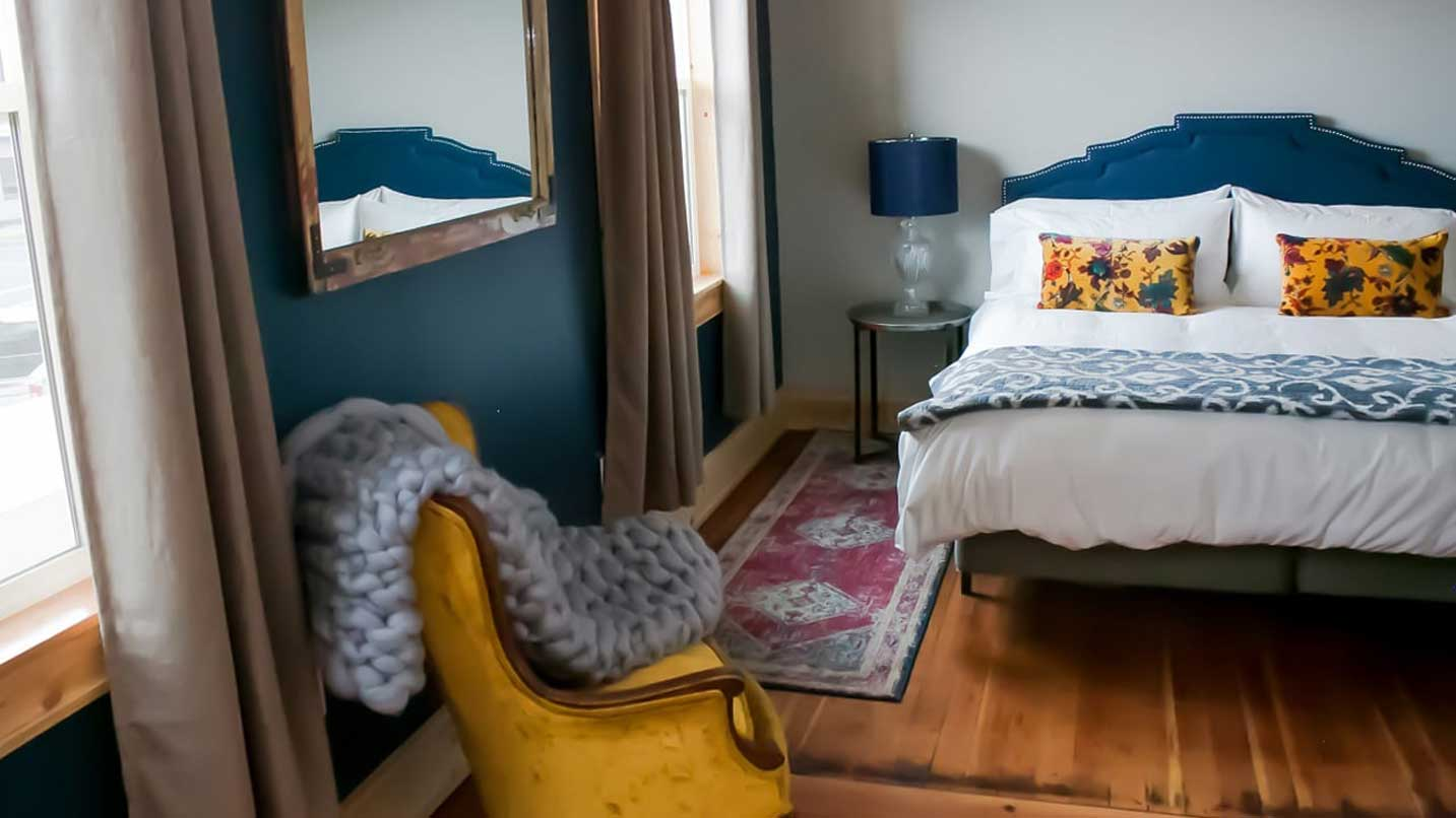 Cozy furniture and colorful decor make this rural hotel room seem urban.